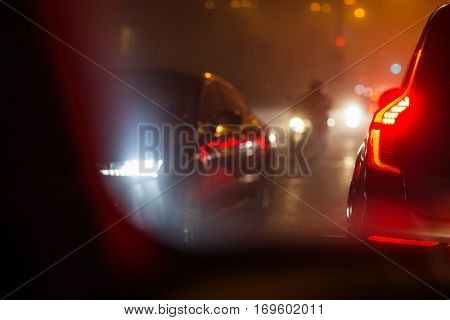 Evening/Night City car traffic - cars on a city road polluting city air with exhaust fumes containing many agents harmful for human health