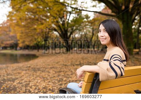 Woman looking far away and sitting at park
