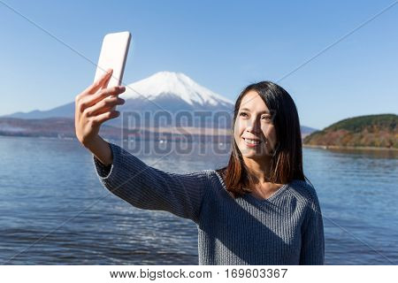 Woman capture photo by herself with mobile phone