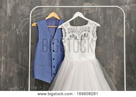 Bride dress and groom suit in dressing room indoors