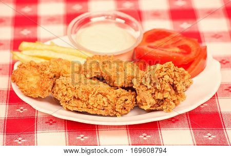 Crispy chicken with white sauce, tomatoes and fries on a white plate