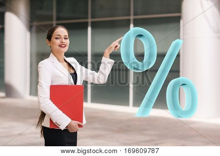 Businesswoman pushing big virtual percent outdoors in front of building.