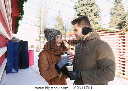 Woman and man drinking coffee on Christmas market