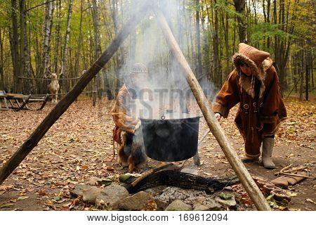 MOSCOW - OCT 18, 2015: Chukchi in their national costumes near fire in ethno-cultural complex Husky Park in Sokolniki