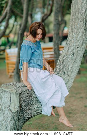 in the park woman in a white skirt and blue blouse barefoot sits on a tree branch