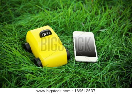 Yellow toy taxi with phone on green grass