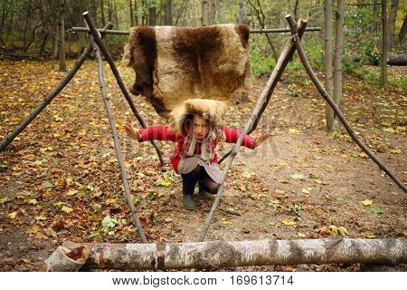 Woman poses under animal skins drying on wooden stakes in Chukchi camp in autumn forest
