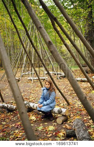Girl sits under wooden frames for wigwams in yellow autumn forest