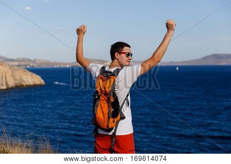 Guy with backpack with hands up on hill in sea background