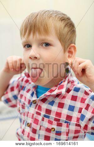 Little handsome blonde boy in checkered shirt grimaces, shallow dof