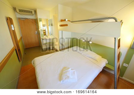 Empty clean stateroom with double bed with top bunk and shower