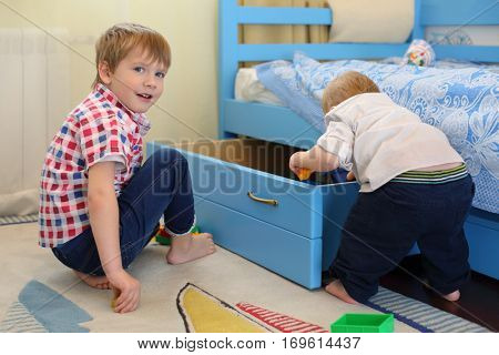 Two little brothers play toys near bed with big drawer in room