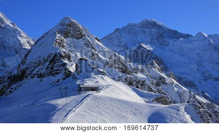 Winter scene in Grindelwald Swiss Alps. Snow covered mountains Lauberhorn and Jungfrau summit station of a cable car.