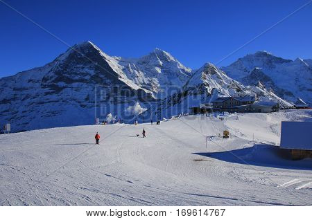 Winter scene in Grindelwald Swiss Alps. Ski and snow covered mountains Eiger Monch Lauberhorn and Jungfrau.