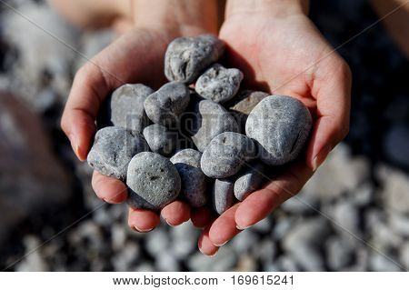 Hands holding sea shingle on beach day