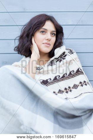 Young beautiful brunette pensive woman wearing nordic style poncho covered in blanket.