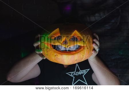 Scary Halloween pumpkins background. Scary glowing faces trick or treat