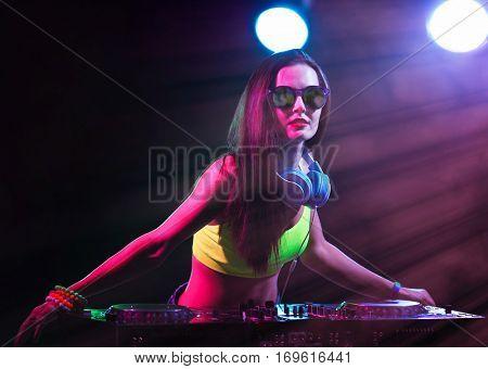 Pretty young DJ playing music in nightclub