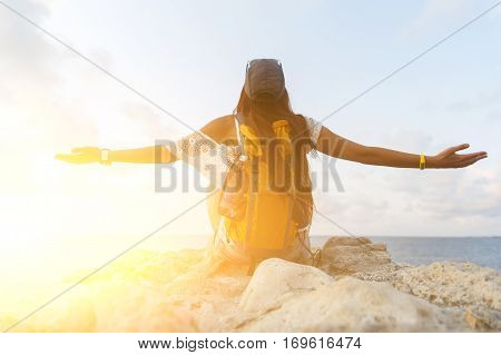 Brunette with backpack sitting back on stone pier on sea