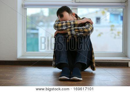 Depressed man sitting on floor near window