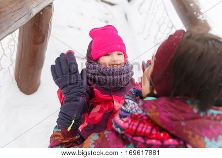 Woman with daughter relaxing in winter park at afternoon