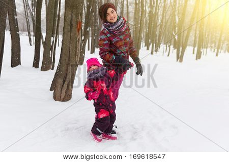 Pastime mother and daughter in wood at winter
