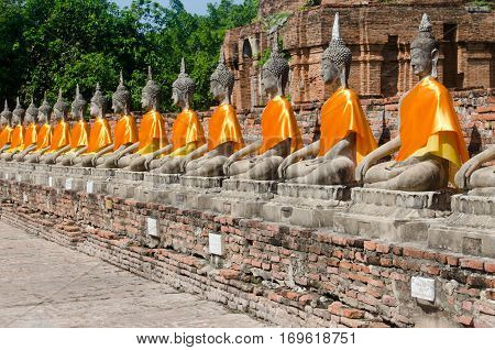 Row of stone Buddhas in seated meditation pose