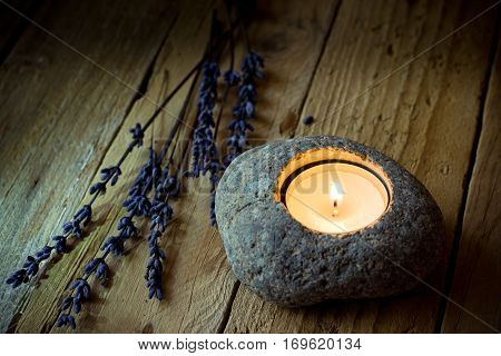 Stone candle holder with tea light on aged wood background, lavender twigs, Easter, peace and tranquility concept, kinfolk