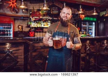 Bearded barman with tattoos wearing an apron standing near the bar and holding a glass of beer poster