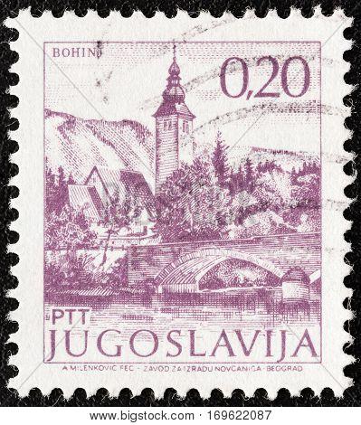 "YUGOSLAVIA - CIRCA 1971: A stamp printed in Yugoslavia from the ""Tourism"" issue shows Bohinj, Slovenia, circa 1971."