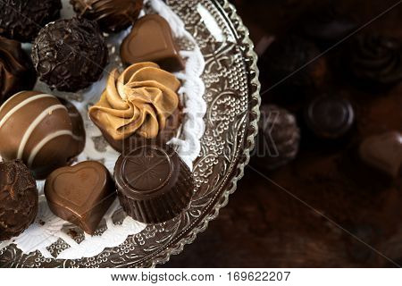 chocolate pralines on an étagère of glass and further blurred underneath on dark rustic wood close up from above selected focus narrow depth of field