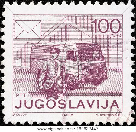 """YUGOSLAVIA - CIRCA 1986: A stamp printed in Yugoslavia from the """"Postal Services"""" issue shows Postman and van, circa 1986."""