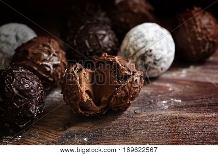 Chocolate assortment of round truffles pralines on dark rustic wood close up with copy space selected focus narrow depth of field