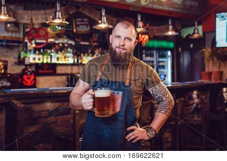 Bearded barman with tattoos wearing an apron standing near the bar and holding a glass of beer