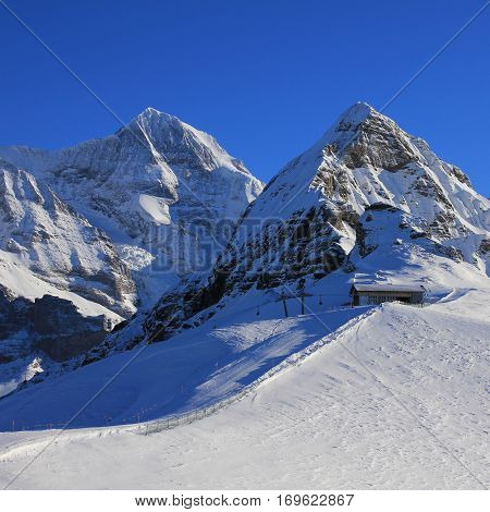 View from the Mannlichen ski area Grindelwald. Snow covered mountains Monch and Lauberhorn. Chair lift and ski slope.