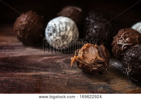 Chocolate assortment of round truffles pralines filled with nougat cream on dark rustic wood close up with copy space selected focus narrow depth of field