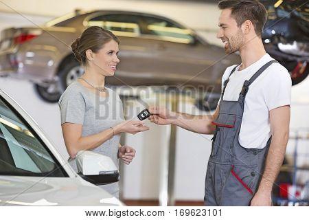 Happy repairman giving car key to woman in workshop