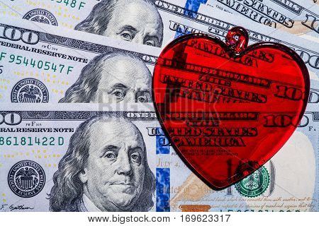 Red glass heart on dollar bills - close up, concept