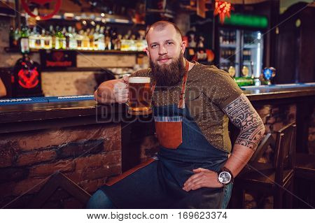 Bearded barman with tattoos wearing an apron sitting near the bar and holding a glass of beer