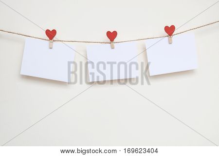Blank card on clothespins with hearts. Mockup for text and beige background. For Valentines Day greetings and love confession