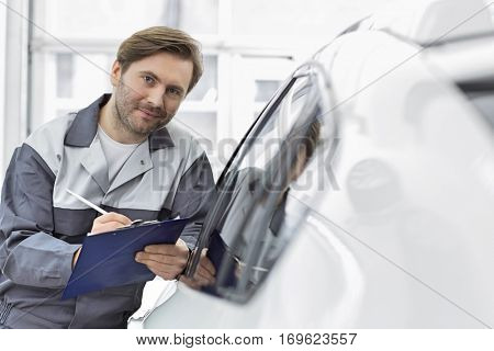 Portrait of confident automobile mechanic holding clipboard while leaning on car's window in workshop