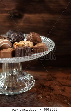 fine chocolate pralines on an elegant glass étagère against a brown wooden background vertical close up selected focus very narrow depth of field