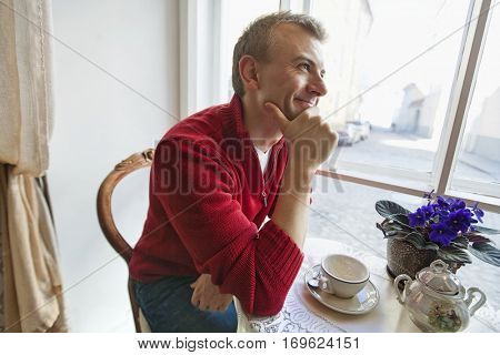 Thoughtful mid adult man sitting at table in cafe