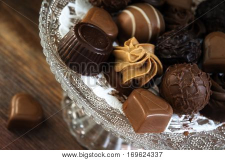 fine chocolate and nougat pralines round and heart shape as a festive gift on a glass étagère on rustic brown wood close up selected focus narrow depth of field