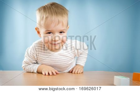 Portrait of a two years old child sitting at the table. Pretty little boy on blue background