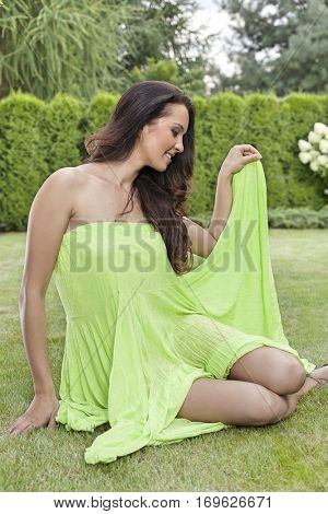 Full length of beautiful young woman in sundress sitting at park