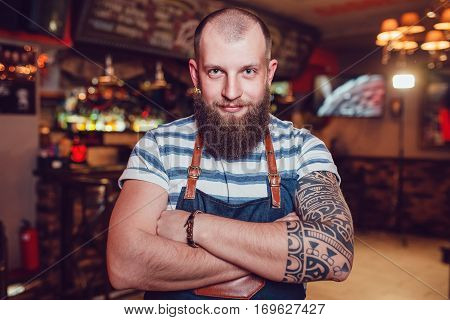 Bearded barman with tattoos wearing an apron standing at the bar with her hands folded.
