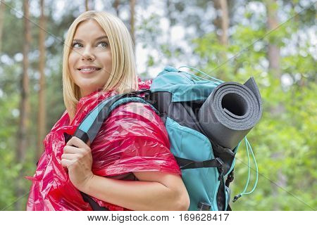 Side view smiling female backpacker in raincoat looking away at forest