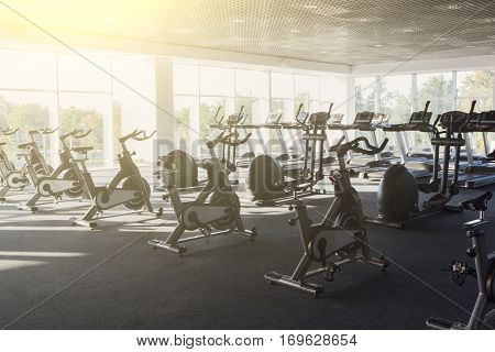 Modern gym interior with equipment. Fitness club with row of training exercise bikes, backlight. Healthy lifestyle concept. Filtered