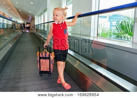 Happy little child with luggage stand on airport transit hall walkway moving to plane departure gate for waiting flight boarding. Active family lifestyle travel by air with kid on summer holiday tour
